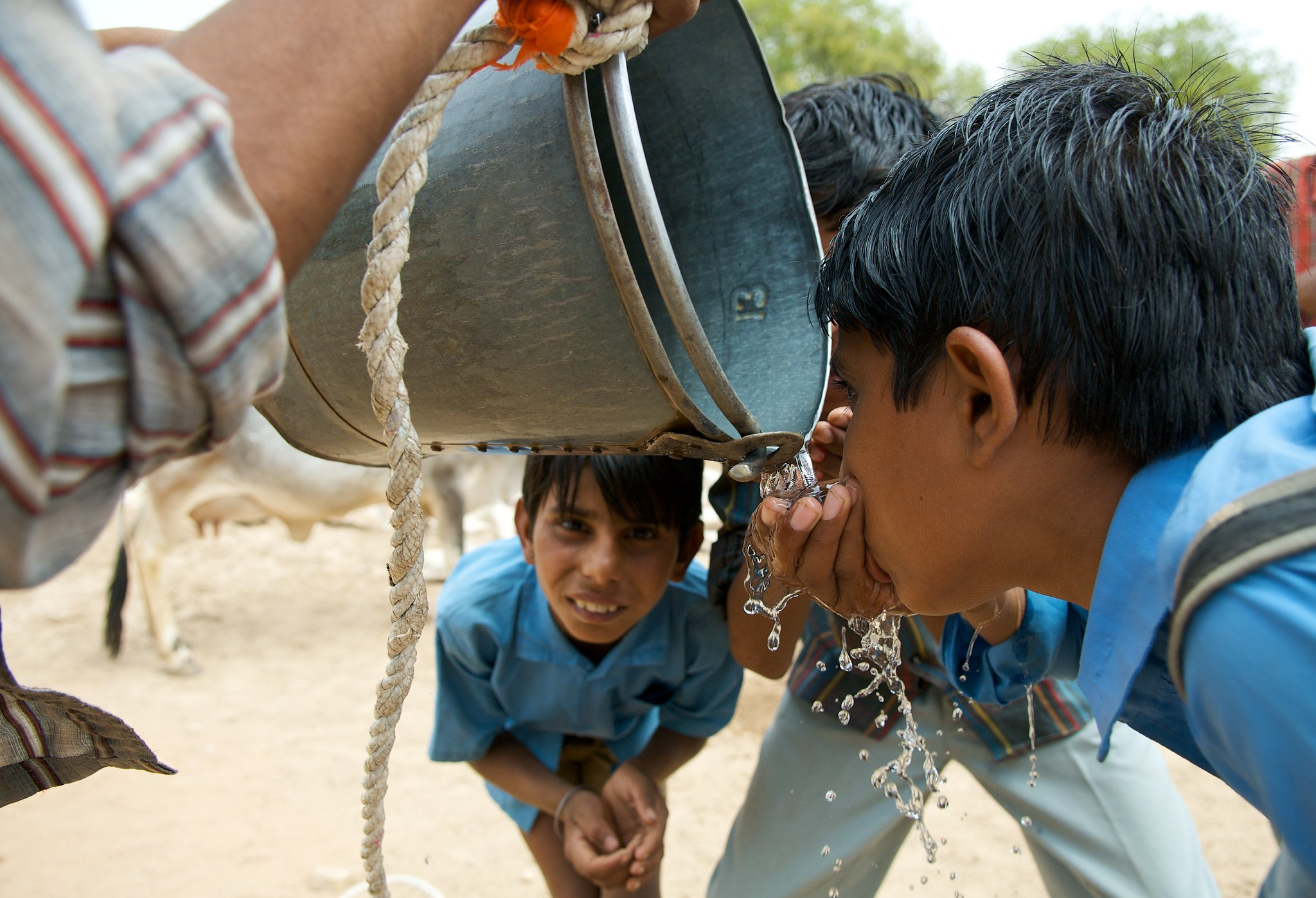 Schuljungen stillen ihren Durst. Sauberes Trinkwasser bekommen sie nur selten. Schuljungen stillen ihren Durst auf dem Nachhauseweg. In einer Region mit Wasserknappheit ist sauberes Trinkwasser selten. | Bild (Ausschnitt): © Daniel Bachhuber [CC BY-NC-ND 2.0]  - flickr